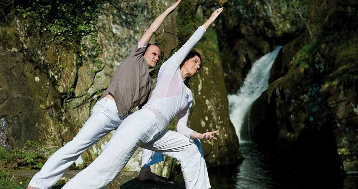 two people doing yoga by waterfall