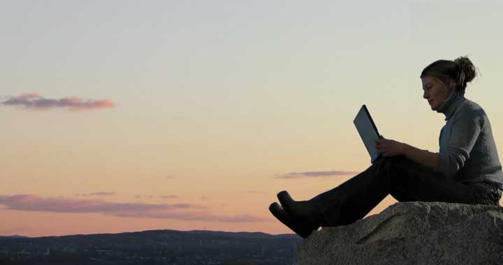 Dru worklife balance - woman using laptop on mountainside